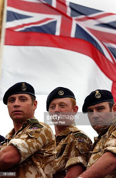 Members of the British Royal Navy stand under the Union Jack flag aboard the HMS Chatham while listening to British Defense Secretary Geoff Hoon...