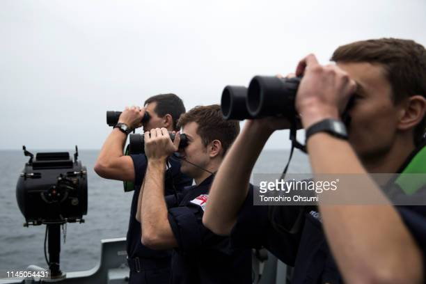 Members of the British Royal Navy use binoculars on the deck of the HMS Montrose frigate as they search for a submarine during a joint exercise with...