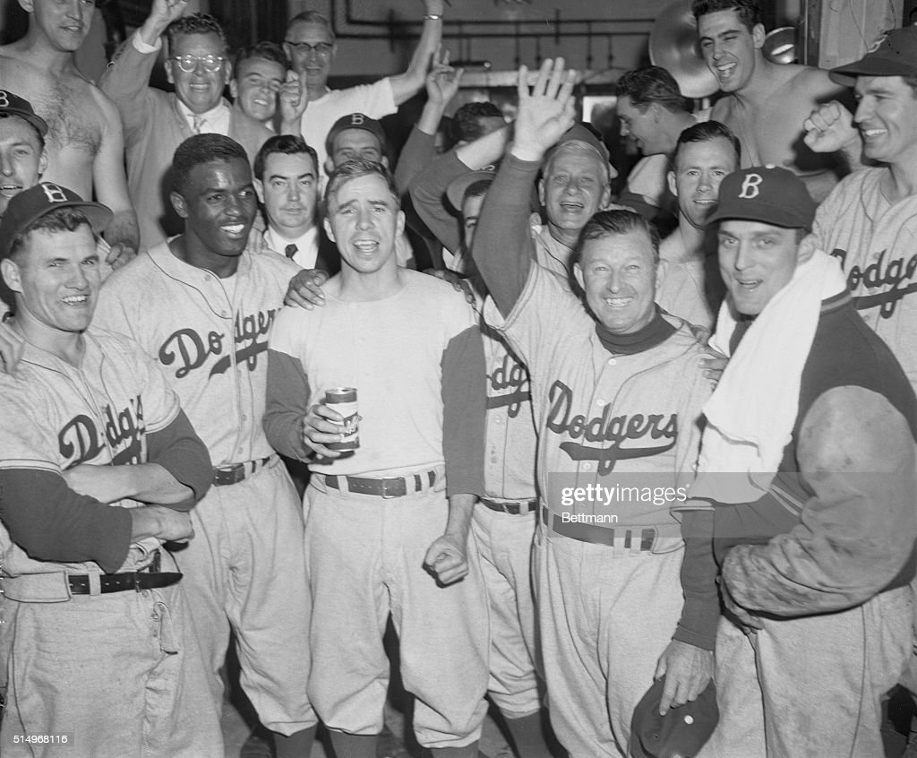 Members of the Brooklyn Dodgers smiled happily, and shouted for joy, in their dressing room after defeating the Philadelphia Phillies 9-8, to tie with the New York Giants for the National League Pennant. Among the happy are left to right: Rocky Bridges; Jackie Robinson, Harold 'Pee Wee' Reese; manager Chuck Dressen; and Carl Erskine.