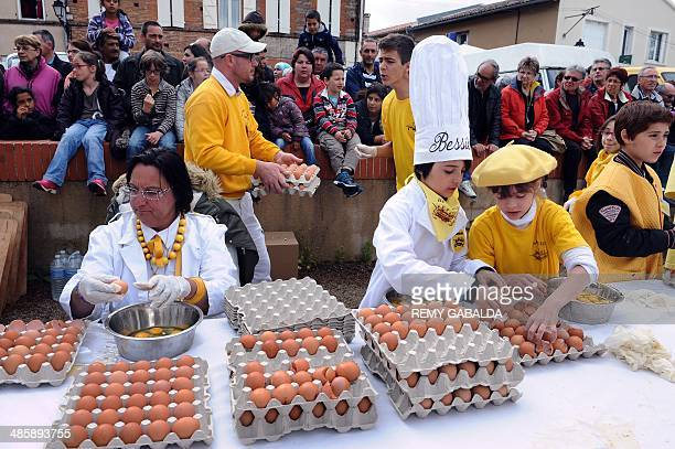 Members of the brotherhood of the Bessieres' giant Easter omelette break thousands of eggs on April 21 2014 in Bessieres southwestern France as part...
