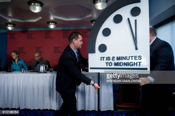 Members of the Bulletin of the Atomic Scientists take their seats after moving their Doomsday clock 30 seconds closer to the end of the world January...