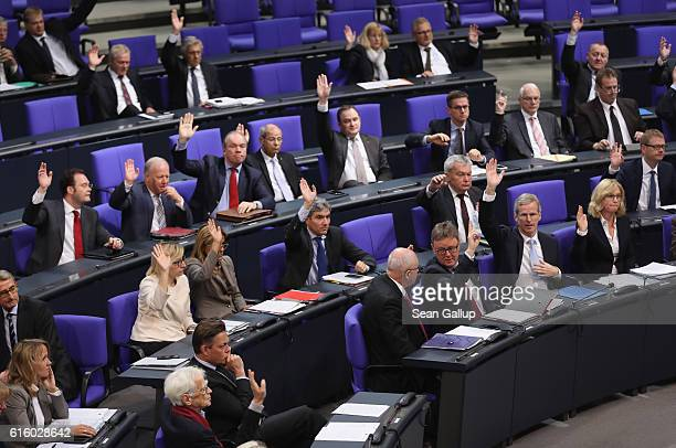 Members of the Bundestag raise their hands in the vote to approve a new law that will expand the legal framework in which Germany's Federal...