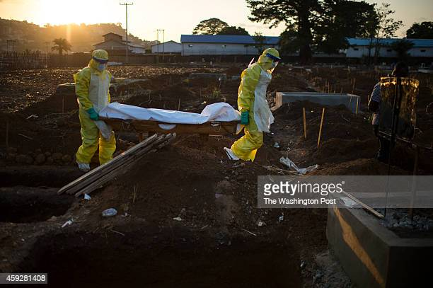 Members of the burial team carry the body of the elderly Alie Fonnah to his grave at King Tom Cemetery in Freetown, Sierra Leone, on Wednesday,...