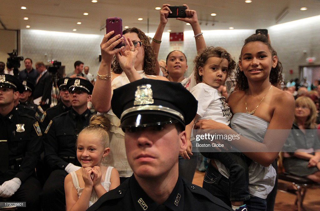 Members of the Caban family photograph relative Yrene Castiilo's graduation from the Boston Police Academy at the I.B.E.W. Hall on Freeport Street in Dorchester.