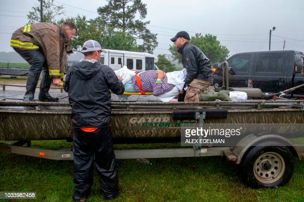 Members of the Cajun Navy and emergency workers place a nursing home patient on a boat during the evacuation of a nursing home due to rising flood...
