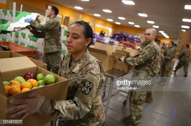 Members of the California National Guard 115th Regional Support Group help pack boxes of fruit and other food at the Second Harvest Food Bank of...