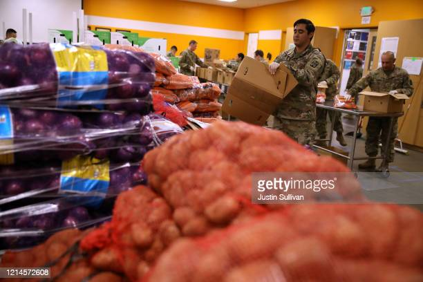 Members of the California National Guard 115th Regional Support Group help pack boxes of onions potatoes and other food at the Second Harvest Food...