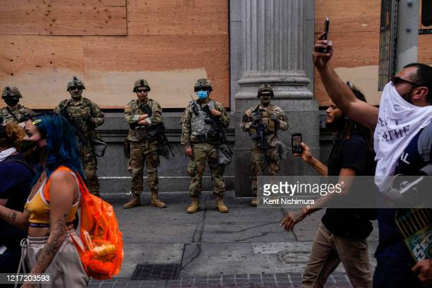 Members of the California National Guard watch as demonstrators march down Spring Street in downtown Los Angeles on Tuesday, June 2, 2020 in Los...