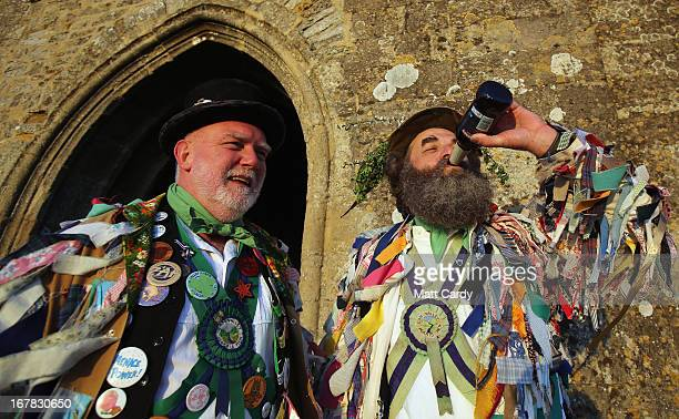 Members of the Cam Valley Morris Men share a beer after they complete their dance at a May Day dawn celebration in front of St Michael's Tower on...