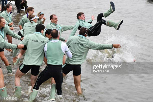 Members of the Cambridge men's boat crew throw their cox Matthew Holland into the River Thames as they celebrate their win in the 165th annual men's...