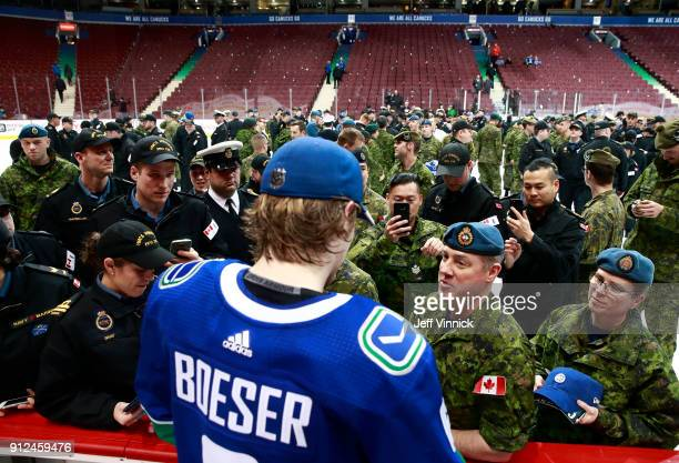 Members of the Canadian Armed Forces line up for autographs from Brock Boeser of the Vancouver Canucks after their NHL game against the Colorado...