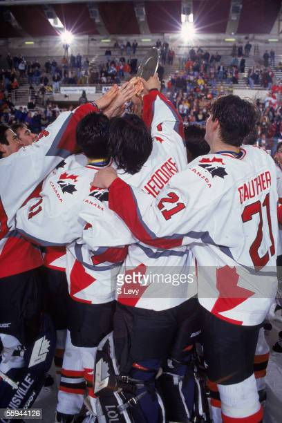 Members of the Canadian national junior hockey team, including goaltender Jose Theodore and defenseman Denis Gauthier , hoist the championship plate...