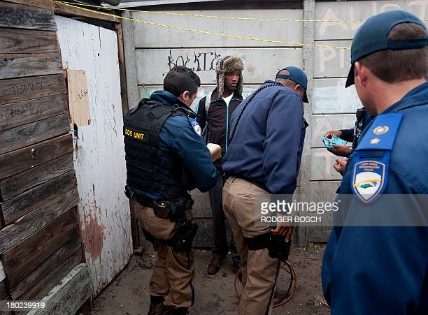 Members of the Cape Town metro police special operations unit seize on August 27 2013 marijuana packed in a blue plastic bag at right from two young...