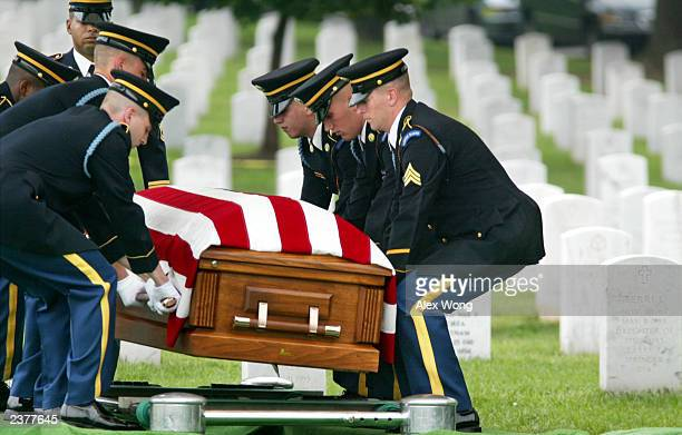 Members of the casket team put down the flagdraped coffin of US Army Specialist Brett Christian at the Arlington National Cemetery August 7 2003 in...