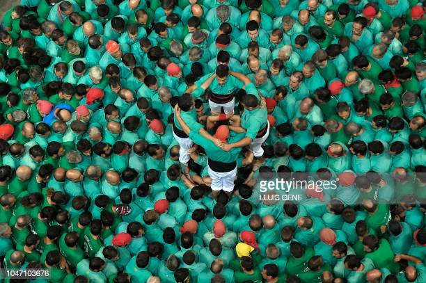 TOPSHOT Members of the Castellers de Vilafranca human tower team form a castell during the XXVII 'castells' competetion in Tarragona on October 7...