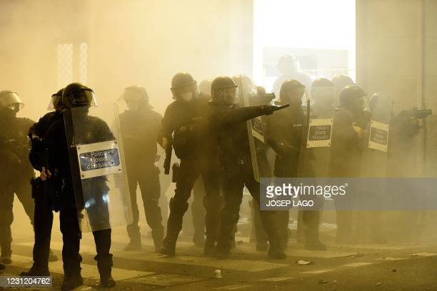 Members of the Catalan regional force Mossos d'Esquadra take position opposite protesters during clashes at a demonstration against the arrest of...