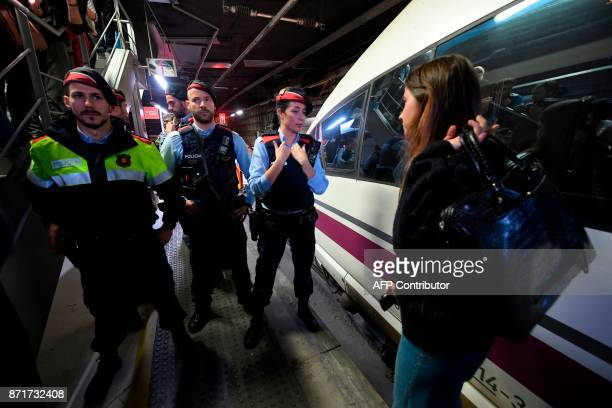 Members of the Catalan regional police force Mossos d'Esquadra stand guard as protesters block train tracks at the Sants Station in Barcelona during...