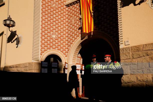 Members of the Catalan regional police force Mossos d'Esquadra stand guard outside a polling station in Vic on December 21 2017 during the Catalan...