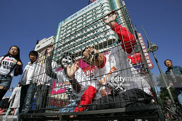 Members of the CCAPN wearing masks of a cat and a dog pose in a cage during a demonstration to call on people to refuse the eating of cats' and dogs'...