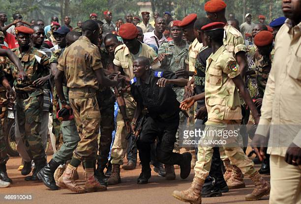 Members of the Central African Armed Forces surround a gendarme suspected of being a former Seleka rebel on February 5 in Bangui as a military...