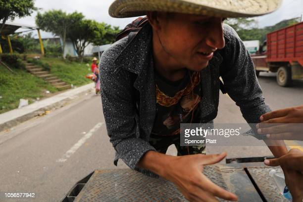 Members of the Central American migrant caravan attempt to get into the back of a truck as they move to the next town on November 02, 2018 in Donaji,...