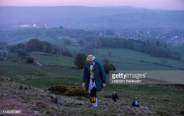 Members of the ChapelenleFrith Morris Dancers climb to the top of the Eccles Pike at High Peak in Derbyshire before sunrise on May 1 2018 The...