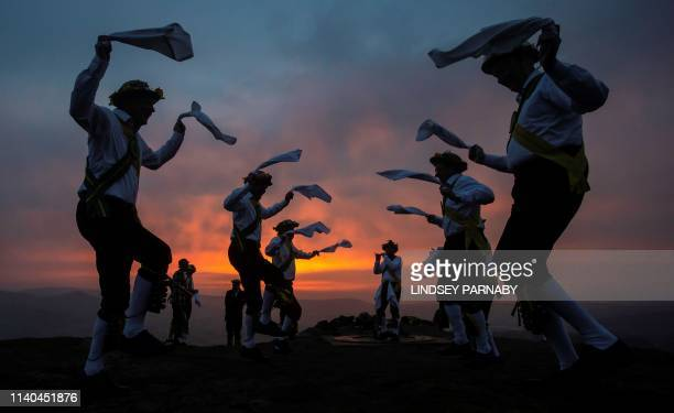 TOPSHOT Members of the ChapelenleFrith Morris Dancers dance atop the Eccles Pike at High Peak in Derbyshire before sunrise on May 1 2018 The...