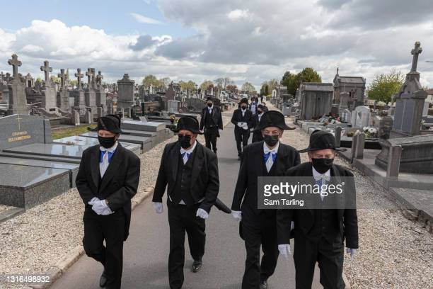 Members of the Charitable Brotherhood of Saint-Eloi in Béthune depart the Northern Cemetery after the burial of Jacques Dufour, an 86-year-old man...