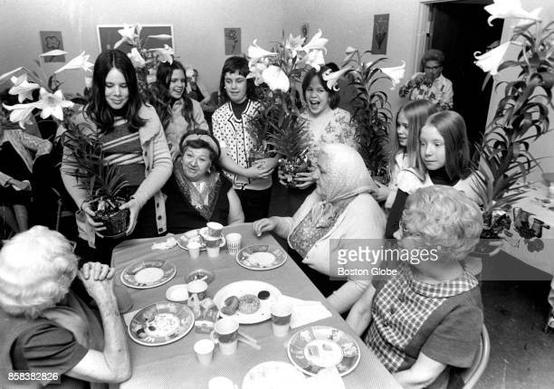 Members of the Charlestown Girls' Club bring lilies to senior citizens at the General Warren Apartments on Washington Street in Boston on Apr 13 1974