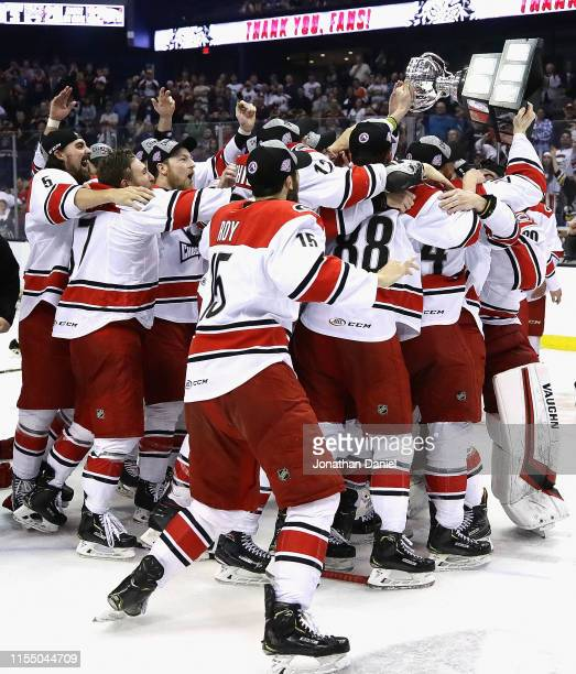 Members of the Charlotte Checkers mob teammate Patrick Brown as he holds the Calder Cup following game Five of the Calder Cup Finals against the...
