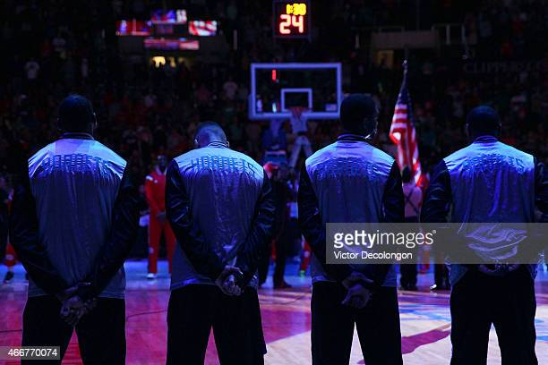 Members of the Charlotte Hornets line up on the court during the singing of the national anthem prior to the NBA game against the Los Angeles...