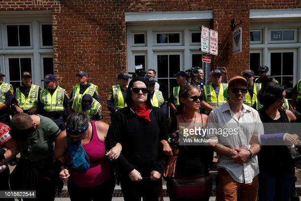 Members of the Charlottesville community and protest groups lock arms in front of police near a makeshift memorial for Heather Heyer who was killed...