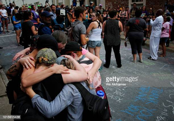 Members of the Charlottesville community and protest groups mourn near a makeshift memorial for Heather Heyer who was killed one year ago during a...