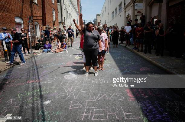 Members of the Charlottesville community gather near a makeshift memorial for Heather Heyer who was killed one year ago during a deadly clash August...