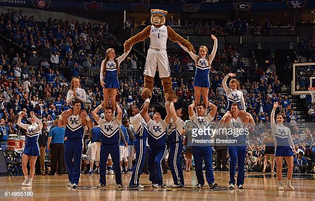 Members of the cheerleading squad of the Kentucky Wildcats and the school mascot make a pyramid during the second half of an SEC Tournament...