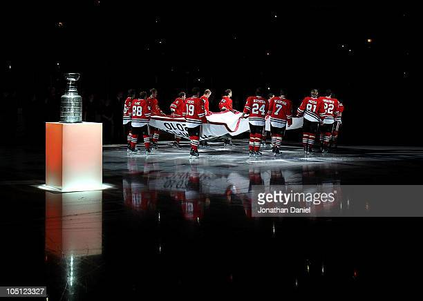 Members of the Chicago Blackhawks carry the Stanley Cup Championship banner across the ice past the Stanley Cup in a ceremony before the Blackhawks...