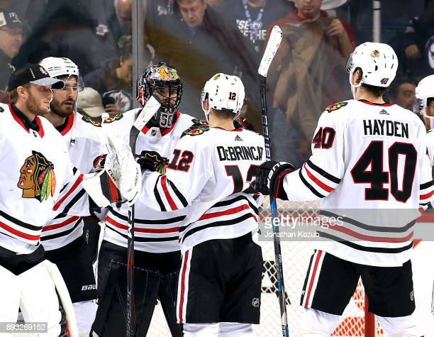 Members of the Chicago Blackhawks congratulate goaltender Corey Crawford following a 51 victory over the Winnipeg Jets at the Bell MTS Place on...