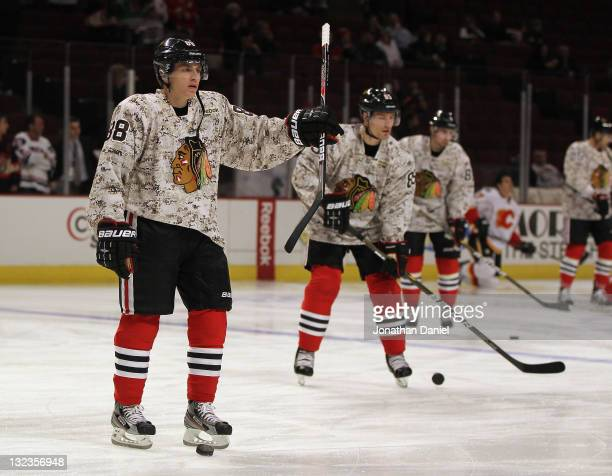 Members of the Chicago Blackhawks including Patrick Kane and Rostislav Olesz wear camouflage jerseys during warmups to honor Veterans Day before a...