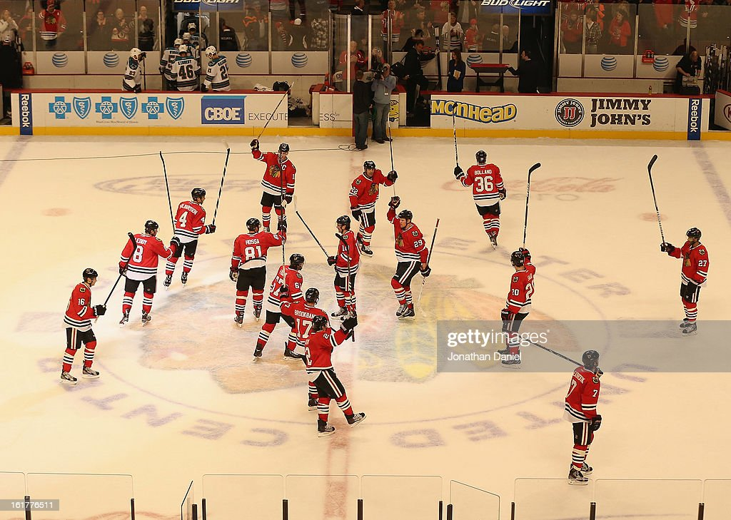 Members of the Chicago Blackhawks salute the crowd after a win over the San Jose Sharks at the United Center on February 15, 2013 in Chicago, Illinois. The Blackhawks defeated the Sharks 4-1.