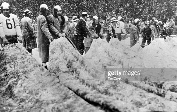 Members of the Chicago Cardinals help the maintenance men clear away the heavy snowwhich delayed the game by a halfhourbefore the 1948 NFL...