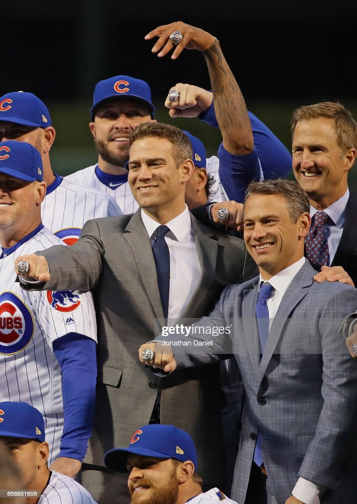 Members of the Chicago Cubs including president Theo Epstein (L) general manager Jed Hoyer and president of business operations Carne Kenny (R) show off their World Series Championship rings before a game against the Los Angeles Dodgers at Wrigley Field on April 12, 2017 in Chicago, Illinois.