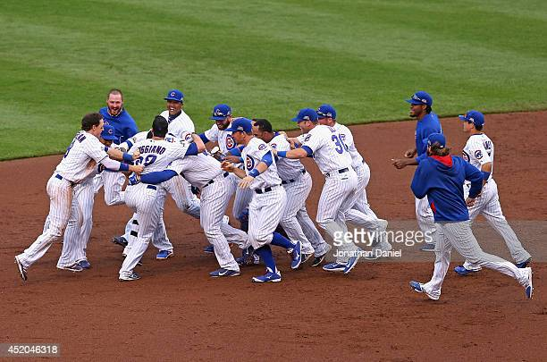 Members of the Chicago Cubs mob Justin Ruggiano after his walkoff single defeated the Atlanta Braves at Wrigley Field on July 11 2014 in Chicago...