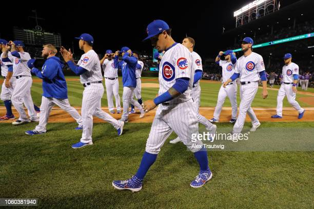 Members of the Chicago Cubs return to the dugout after the national anthem before the National League Wild Card game against the Colorado Rockies at...