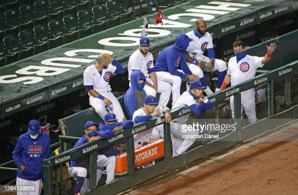 Members of the Chicago Cubs watch from the dugout as teammates take on the Kansas City Royals at Wrigley Field on August 03, 2020 in Chicago,...