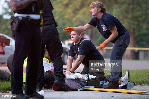 Members of the Chicago Fire Department work on a gunshot victim at the scene of a double shooting in Ogden Park Monday Labor Day Sept 5 in the...