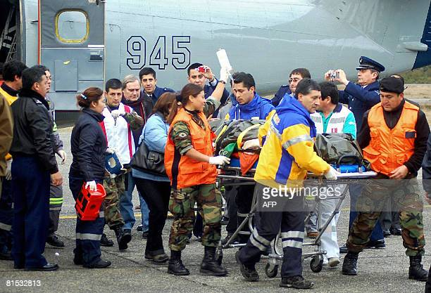 Members of the Chilean Air force help upon the arrival on June 11 2008 in Puerto Montt Chile one of the survivors of a light aircraft that crashed...