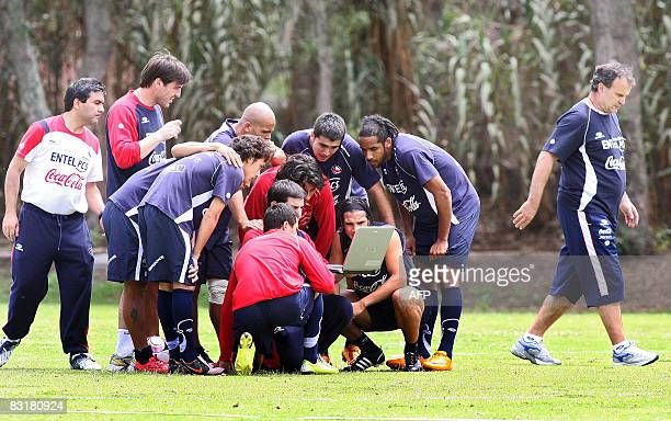 Members of the Chilean national football team huddle around a laptop as coach Marcelo Bielsa walks away from the group during a training session at...