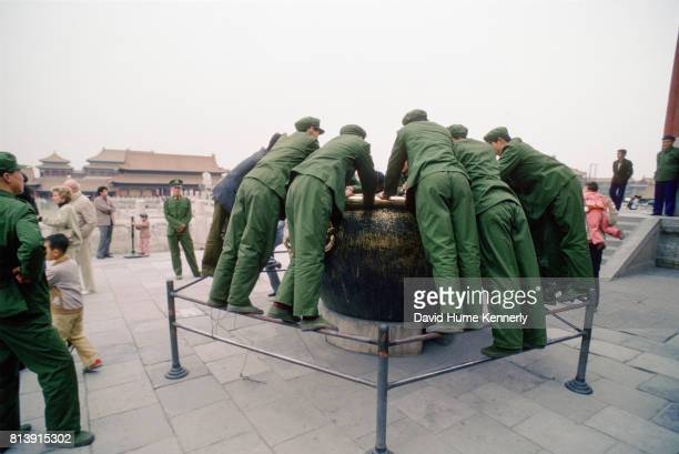 Members of the Chinese Army examine a cauldron on Tiananmen Square Beijing China April 15 1989