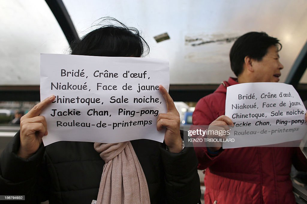 Members of the Chinese community in France hold posters with derogatory mentions and insults during a demonstration against xenophobia called by the association 'Francais de Chine, Chinois de France' (French from China, Chinese of France) on November 21, 2012 near the French newspaper Le Parisien's headquarters in Saint-Ouen, a northern suburb of Paris. Demonstrators denounce the stereotypes their community is subjected to after Le Parisien published on November 11 a special issue on the Chinese mafia in France.