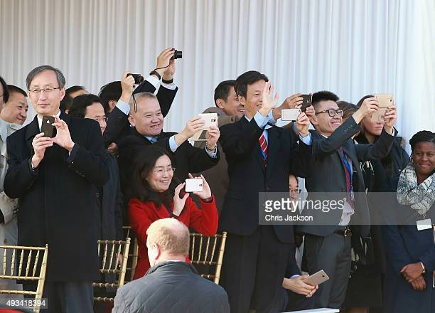 Members of the Chinese delegation take photographs on smart phones as Queen Elizabeth II and Chinese President Xi Jinping board the carriage during...